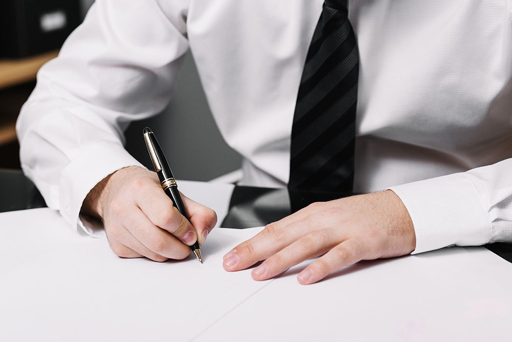 man in business clothes writing a check