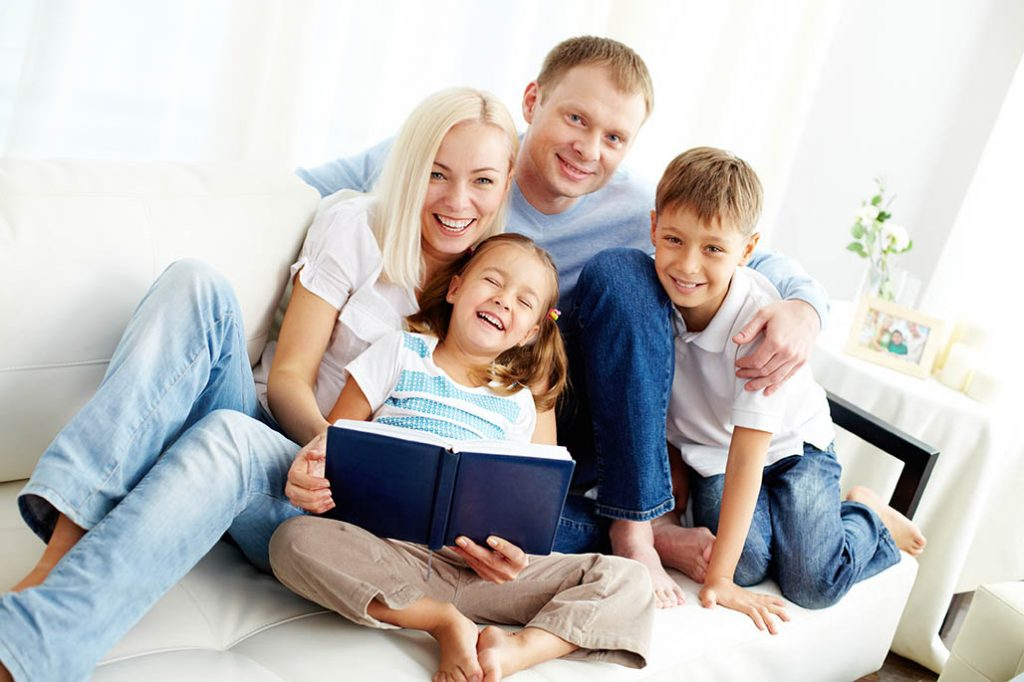 a family sitting together happily reading a book