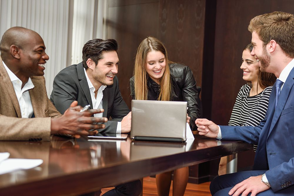 a group of people in an office looking at a laptop