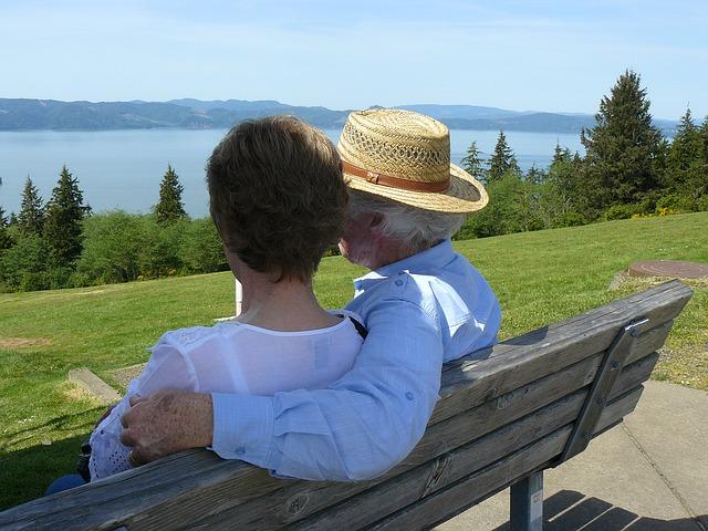 older couple sitting together on a park bench