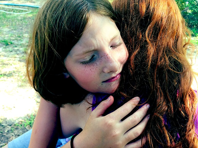 a young girl giving her mother a hug