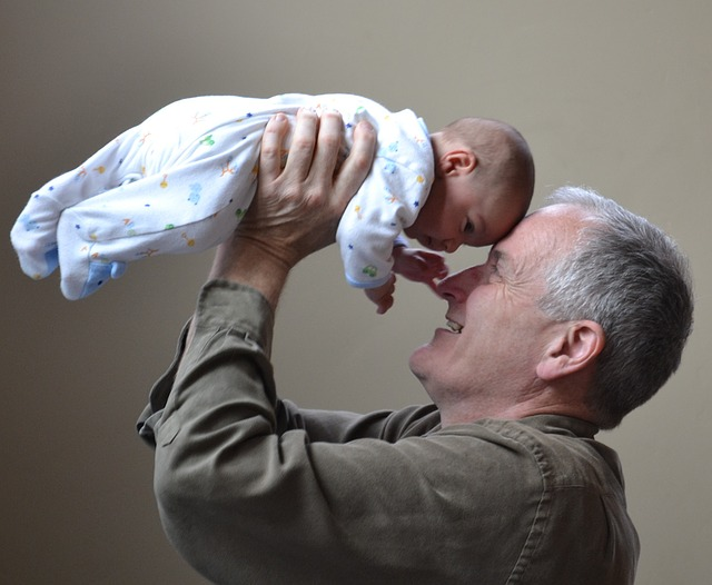 Smiling father holding his baby to his head