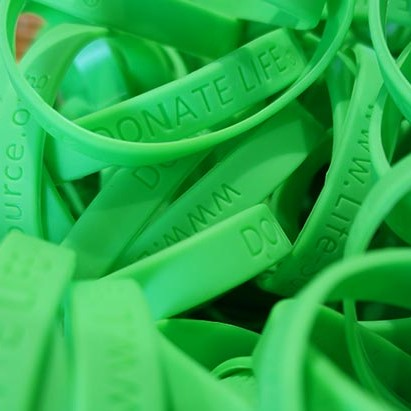 a pile of green Donate Life rubber bracelets