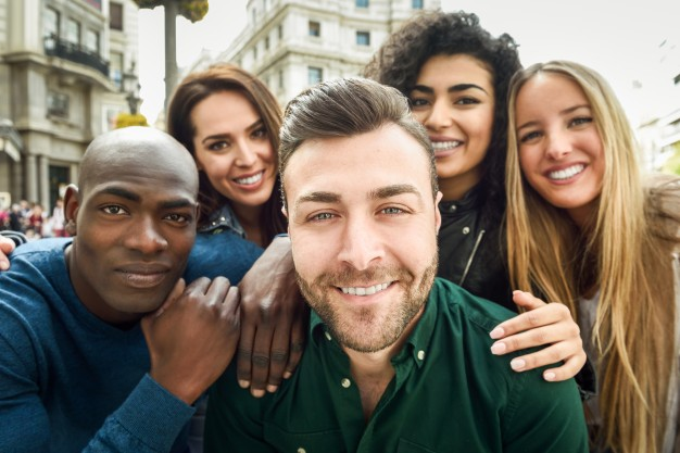 multiracial group of young people taking a selfie together